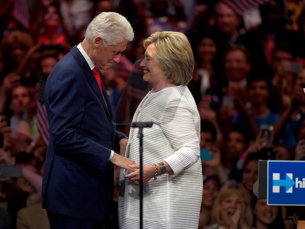 """. Democratic presidential candidate Hillary Clinton stands on stage with husband, former US president Bill Clinton during her primary night event at the Duggal Greenhouse, Brooklyn Navy Yard, June 7, 2016 in New York.  Hillary Clinton hailed a historical \""""milestone\"""" for women as she claimed victory over rival Bernie Sanders in the Democratic White House nomination race. \""""Thanks to you, we\'ve reached a milestone,\"""" she told cheering supporters at a rally in New York. \""""The first time in our nation\'s history that a woman will be a major party\'s nominee.\"""" (TIMOTHY A. CLARY/AFP/Getty Images)"""
