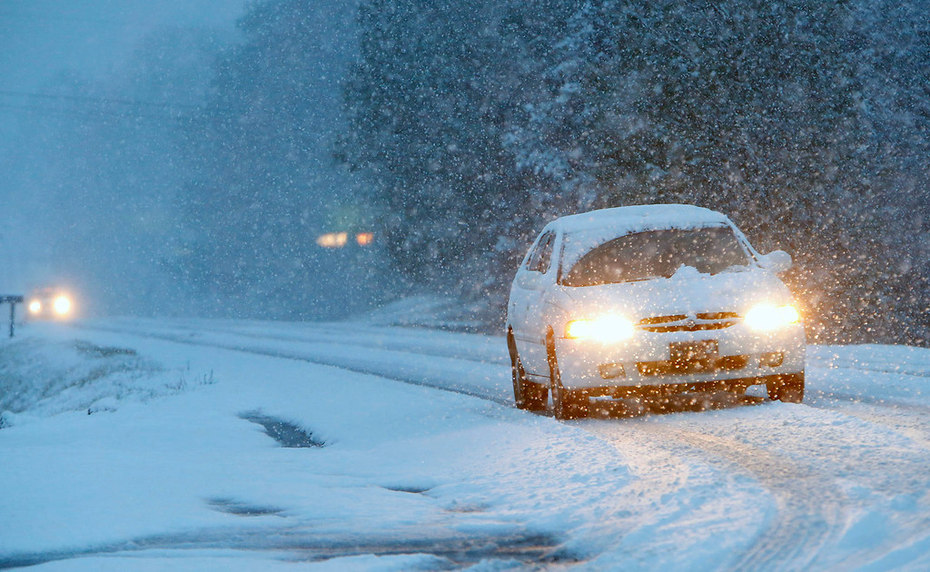 . Vehicles slowly make their way on a snow-covered Alabama state Route 35, on Tuesday, Feb. 11, 2014, in Fort Payne, Ala. Residents woke to a blanket of snow that was expected to continue throughout the morning hours. (AP Photo/Hal Yeager)