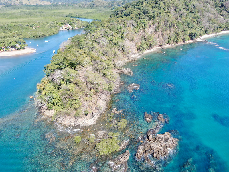 Lush Tropical coastline with rocks and blue water in Costa Rica
