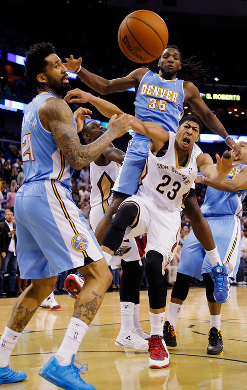 . New Orleans Pelicans power forward Anthony Davis (23) fights for a loose ball with Denver Nuggets small forward Wilson Chandler (21), and Denver Nuggets power forward Kenneth Faried (35) in the second half of an NBA basketball game in New Orleans, Sunday, March 9, 2014. The Pelicans defeated the Nuggets 111-107. Davis scored 32-points in the Pelicans victory. (AP Photo/Bill Haber)