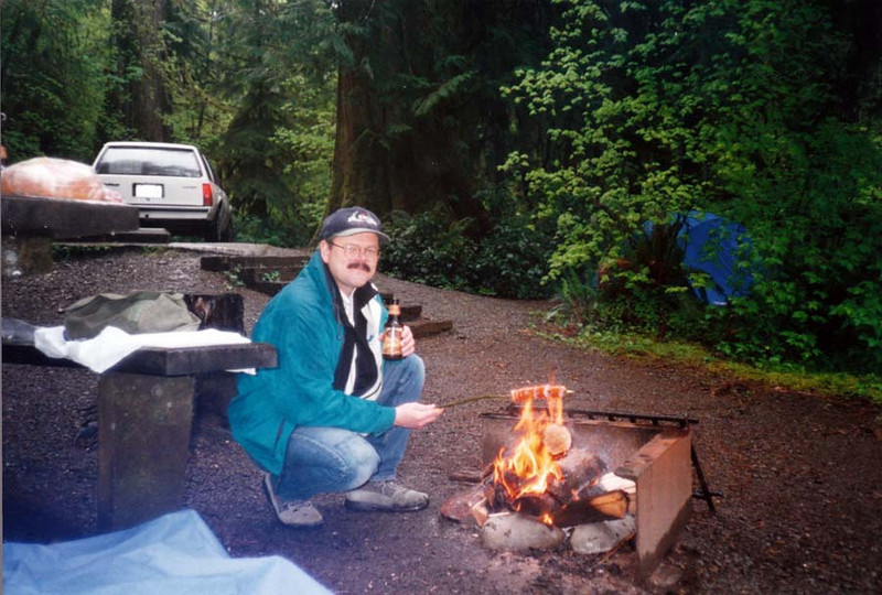 TOASTING MARSHMALLOWS Roasted marshmallows and beer, the Breakfast of Champions. It doesn't get much better than that, huh? This is the camping trip where I almost set my fleece jacket's sleeve on fire -- while wearing it! Lisa later cut off the sleeves and made a vest out of it, which she kept.