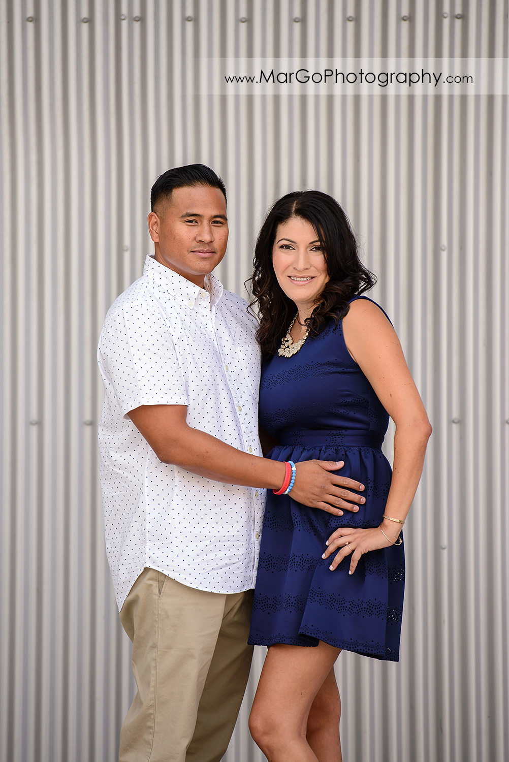 portrait of woman in blue dress and man in white shirt holding hands looking into camera on the metal wall during engagement session at San Jose San Pedro Square Market