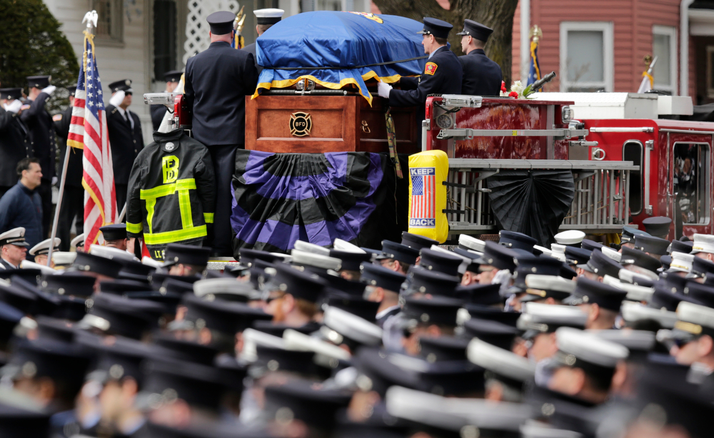 Description of . Firefighters salute as the casket of Boston Fire Lt. Edward Walsh is carried on Engine 33 as the funeral procession departs St. Patrick's Church in Watertown, Mass., Wednesday, April 2, 2014. Walsh and his colleague Michael Kennedy died after being trapped while battling a nine-alarm apartment fire in Boston on March 26. (AP Photo/Charles Krupa)