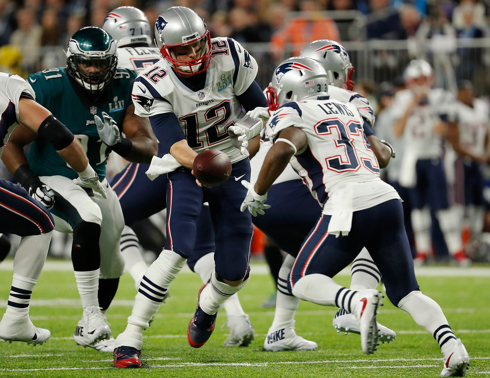 . New England Patriots quarterback Tom Brady (12) hands the ball to running back Dion Lewis (33), during the first half of the NFL Super Bowl 52 football game against the Philadelphia Eagles, Sunday, Feb. 4, 2018, in Minneapolis. (AP Photo/Charlie Neibergall)