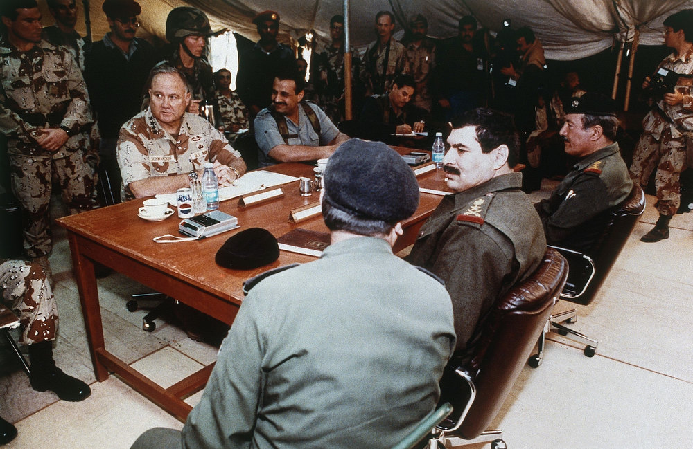 Description of . U.S. Gen. H. Norman Schwarzkopf, left, and Saudi Gen. Khalid Bin Sultan, both seated at table facing camera, prior to the start of a meeting with Iraqi military leaders, foreground, to set the terms for a permanent cease-fire. Third from right in foreground is Iraqi Lt. Gen. Sultan Hasheem Ahmad. The meeting was held Sunday, March 3, 1991 at a captured Iraqi air base at Safwan, Iraq. (AP Photo/Pool )