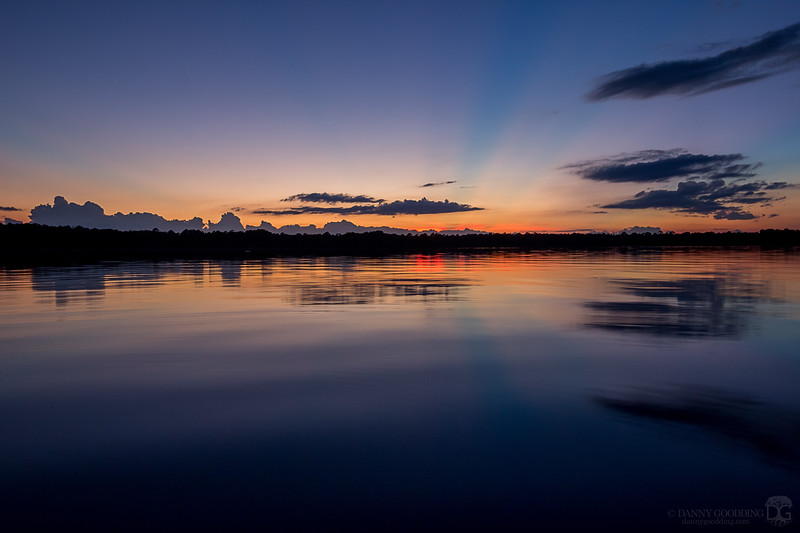 Crepuscular rays at sunset over a lake