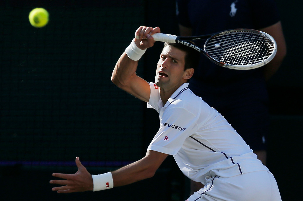 . Novak Djokovic of Serbia plays a return to Roger Federer of Switzerland during their men\'s singles final match at the All England Lawn Tennis Championships in Wimbledon, London, Sunday, July 6, 2014. (AP Photo/Pavel Golovkin)
