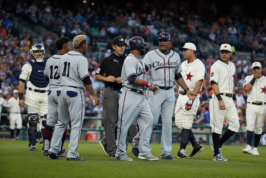 . Cleveland Indians first base coach Sandy Alomar Jr., center right, gets between Carlos Santana, center, and Detroit Tigers second baseman Ian Kinsler, second from right, after Santana was hit by a pitch during the fifth inning in the second baseball game of a doubleheader in Detroit, Saturday, July 1, 2017. (AP Photo/Rick Osentoski)