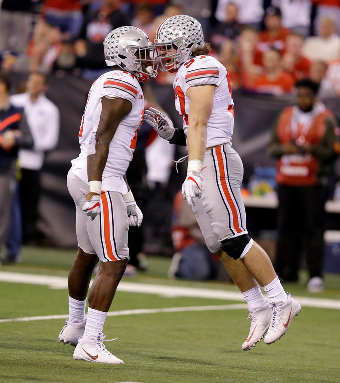 . Ohio State\'s Nick Bosa, right, and Jalyn Holmes celebrate after Wisconsin quarterback Alex Hornibrook was sacked during the second half of the Big Ten championship NCAA college football game, Saturday, Dec. 2, 2017, in Indianapolis. (AP Photo/Michael Conroy)