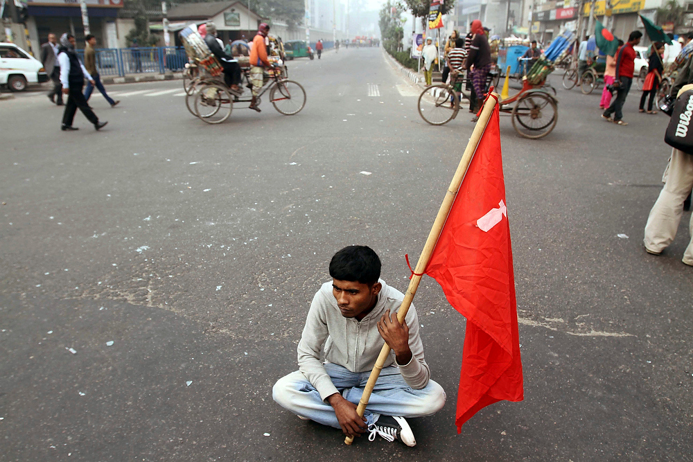 Description of . A member of a coalition of five leftist parties sits on a road holding his party flag during a nationwide strike in Dhaka, Bangladesh, on Tuesday, Dec. 18, 2012. A general strike to demand that Muslim-majority Bangladesh ban Islamic political parties shut down schools and stores and disrupted traffic in the capital on Tuesday. (AP Photo/Pavel Rahman)