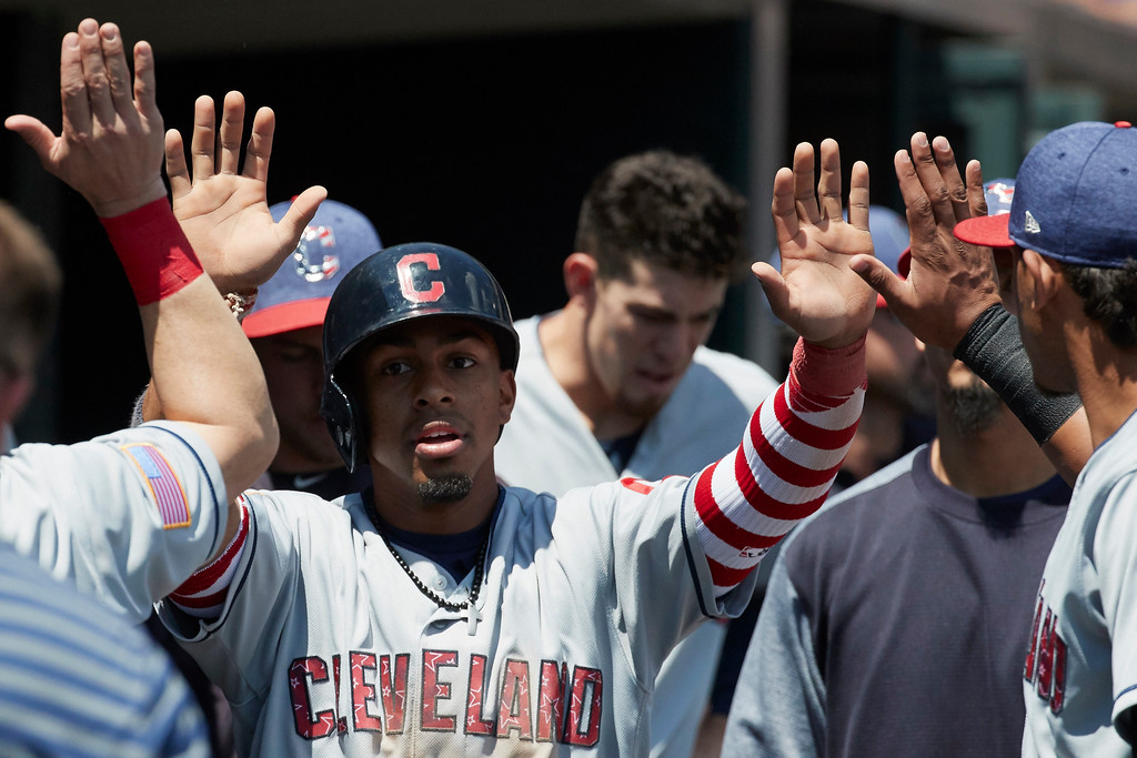 . Cleveland Indians\' Francisco Lindor, center, is congratulated by teammates after scoring against the Detroit Tigers in the fourth inning of a baseball game in Detroit, Sunday, July 2, 2017. (AP Photo/Rick Osentoski)