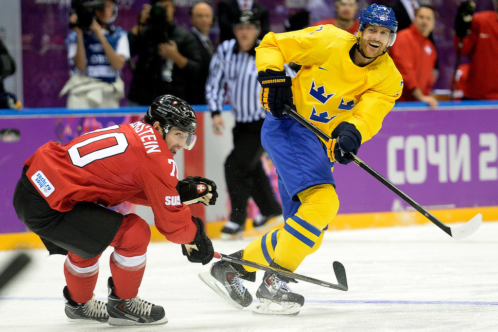 . Sweden\'s Henrik Tallinder takes a shot around Switzerland\'s Denis Hollenstein during the action at Bolshoy Arena. Sochi 2014 Winter Olympics on Friday, February 14, 2014. (Photo by AAron Ontiveroz/The Denver Post)