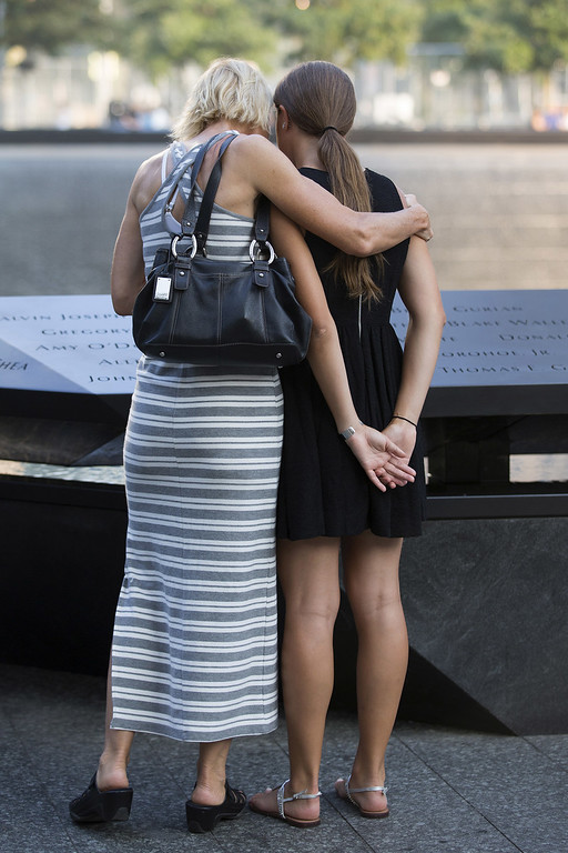 . Women pause at the Cantor Fitzgerald section of the reflecting pool at the 9/11 Memorial before ceremonies for the 12th anniversary of the terrorist attacks on lower Manhattan at the World Trade Center site on September 11, 2013 in New York City. (Photo by Ozier Muhammad-Pool/Getty Images)