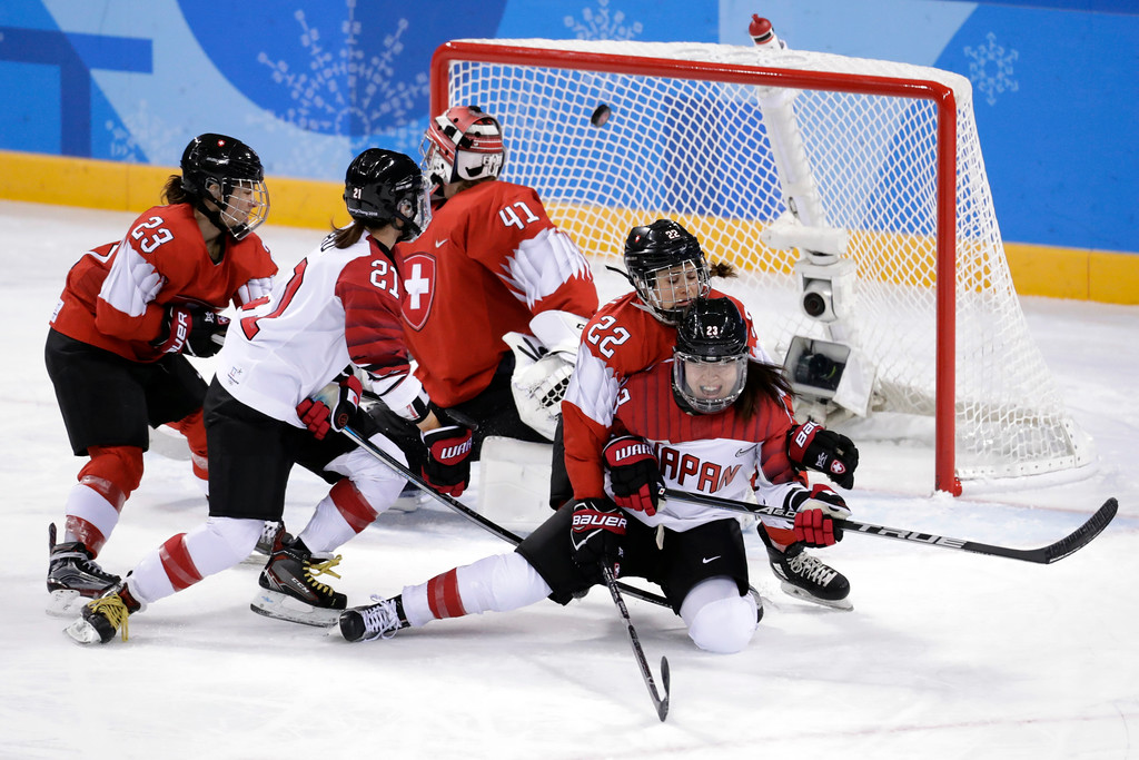 . Hanae Kubo (21), of Japan, scores a goal as Livia Altmann (22), of Switzerland, checks Ami Nakamura (23) during the third period of the preliminary round of the women\'s hockey game at the 2018 Winter Olympics in Gangneung, South Korea, Monday, Feb. 12, 2018. (AP Photo/Julio Cortez)