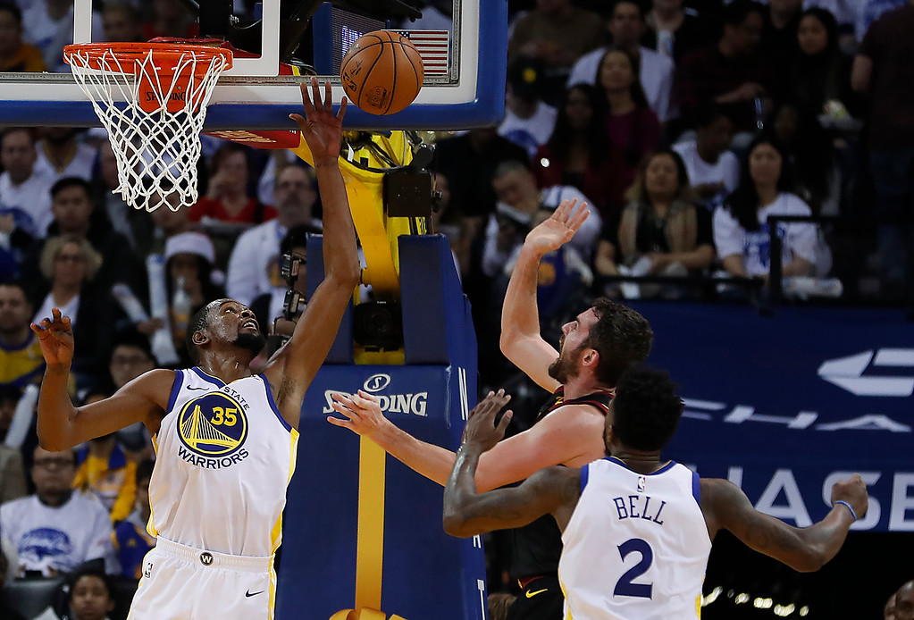 . Golden State Warriors forward Kevin Durant (35) blocks a shot by Cleveland Cavaliers forward Kevin Love (0) during the second half of an NBA basketball game in Oakland, Calif., Monday, Dec. 25, 2017. The Warriors won 99-92. (AP Photo/Tony Avelar)