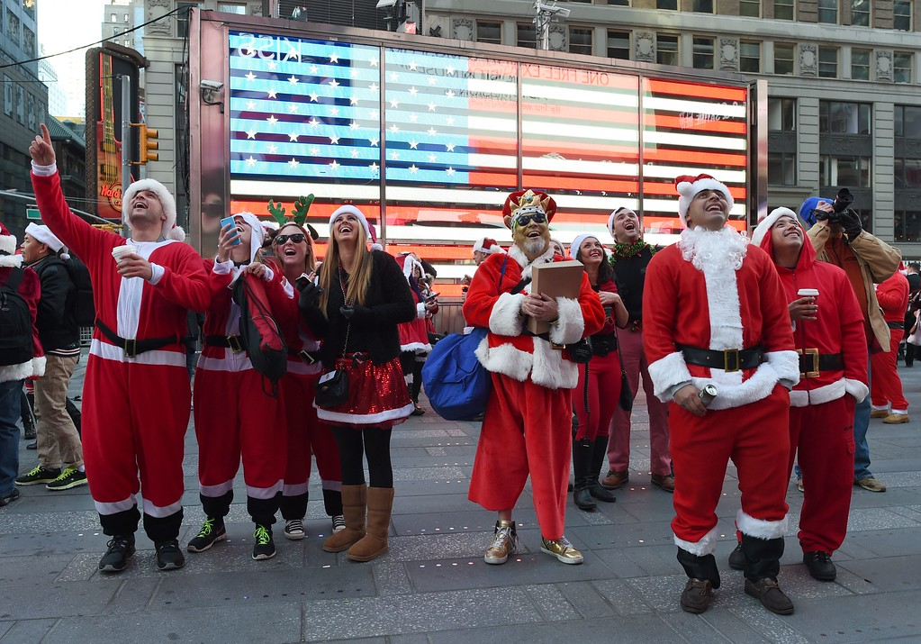 . Santas look at themselves on the big screen TV in Times Square as hundreds of Santas gather for the annual Santacon festivities on December 13, 2014 in New York. AFP PHOTO/DON EMMERT/AFP/Getty Images