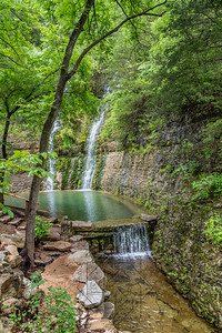 Two waterfalls cascading down the canyon walls into a reflection pond with summer foliage
