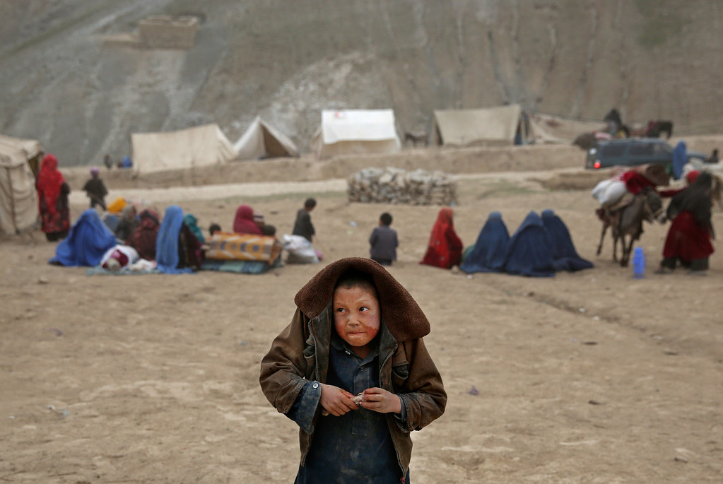 . In this Sunday, May 4, 2014 photo, an Afghan child protects himself from the rain, near the site of Friday\'s landslide that buried Abi-Barik village in Badakhshan province, northeastern Afghanistan.  (AP Photo/Massoud Hossaini)