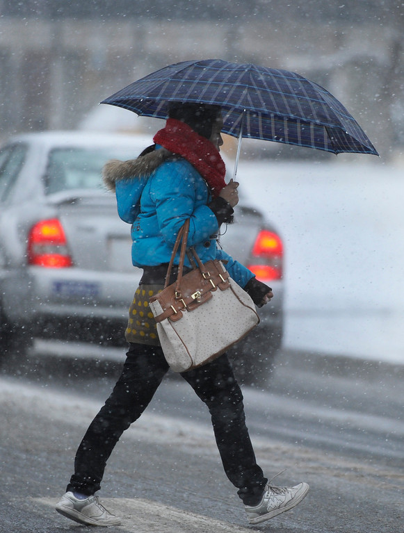 . DENVER, CO. - FEBRUARY 20:  An umbrella became very useful to a pedestrian crossing East Asbury Street on the University of Denver campus as heavy wet snow started to fall in the Wednesday evening, February 20, 2013. The Denver metro area is expecting 4-6 inches overnight. (Photo By Karl Gehring/The Denver Post)