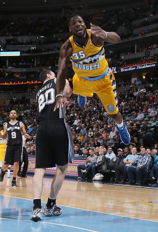. Denver Nuggets forward Kenneth Faried, front, is sent flying as he is fouled by San Antonio Spurs guard Manu Ginobili (20), of Argentina, while driving the lane for a shot in the first quarter of an NBA basketball game in Denver, Friday, March 28, 2014. (AP Photo/David Zalubowski)