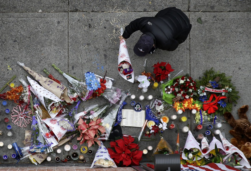 . A man leaves flowers at an impromptu memorial near the site where two police officers were killed the day before in the Brooklyn borough of New York, Sunday, Dec. 21, 2014. Police say Ismaaiyl Brinsley ambushed officers Rafael Ramos and Wenjian Liu in their patrol car in broad daylight Saturday, fatally shooting them before killing himself inside a subway station. (AP Photo/Seth Wenig)