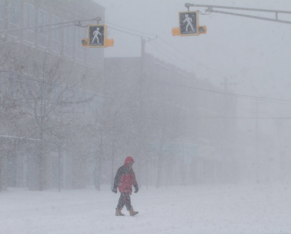 . A man walks in downtown Charlottetown, Canada, during a snow storm on Tuesday morning, Jan. 27, 2015. Flights were canceled and schools, government offices and universities throughout the Maritimes were closed as a powerful winter storm unleashed stiff winds and brought heavy snowfall to the region.  (AP Photo/The Canadian Press, John Morris)