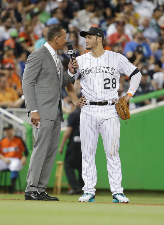 . Former player and TV commentator Alex Rodriguez, left, speaks with National League\'s Colorado Rockies third baseman Nolan Arenado (28), during the first inning at the MLB baseball All-Star Game, Tuesday, July 11, 2017, in Miami. (AP Photo/Lynne Sladky)