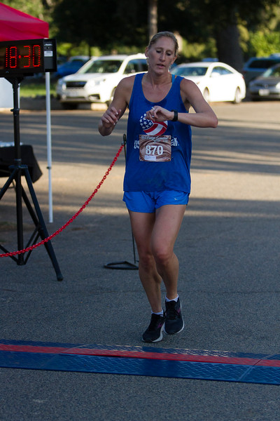 Jennifer Marquez (870) checks her watch as she crosses the finish line at the 2nd Annual Visalia Hot Fudge Sundae 5K  Run. Ms. Marquez was the overall women's winner in a time of  18:31.4.