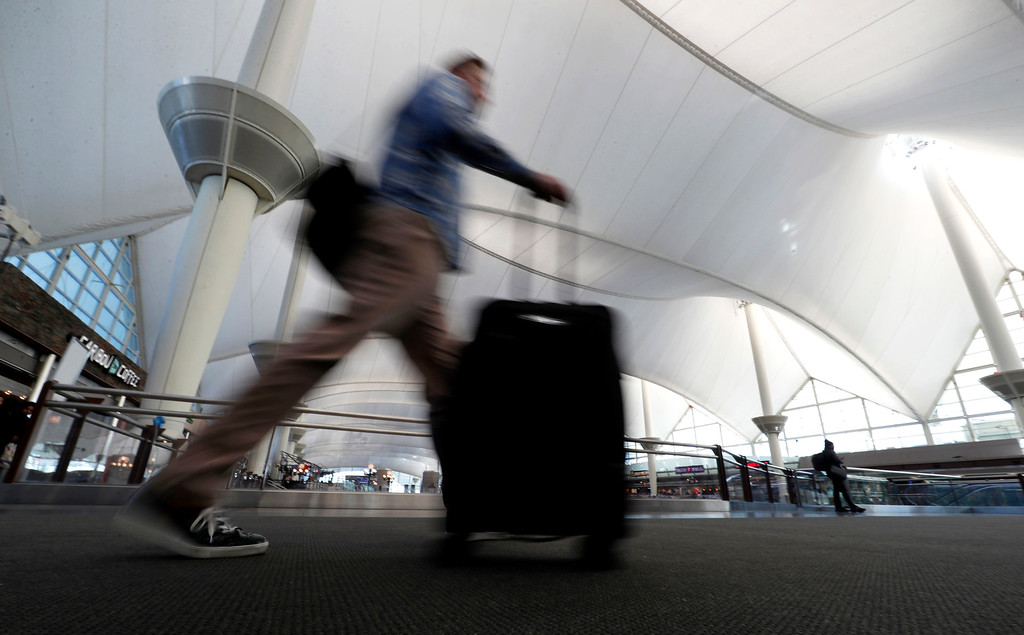 . A traveler hurries along a bridge beneath the canopy roof of the terminal at Denver International Airport early Wednesday, Nov. 23, 2016, in Denver. Travelers are criss-crossing the country Wednesday, clogging airport terminals in a rush to reach their Thanksgiving Day destinations. (AP Photo/David Zalubowski)