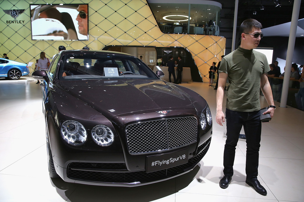 . A potential consumer stands beside a Bentley Flying Spur V8 car during the 2014 Beijing International Automotive Exhibition at China International Exhibition Center on April 21, 2014 in Beijing, China.   (Photo by Feng Li/Getty Images)