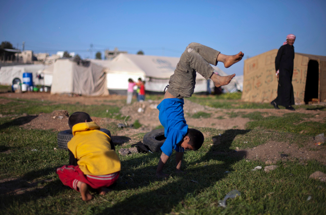 . In this Friday, April 4, 2014 photo, Syrian boys play in an unofficial refugee camp on the outskirts of Amman, Jordan. Some residents, frustrated with Zaatari, the region\'s largest camp for Syrian refugees, set up new, informal camps on open lands, to escape tensions and get closer to possible job opportunities.(AP Photo/Khalil Hamra)