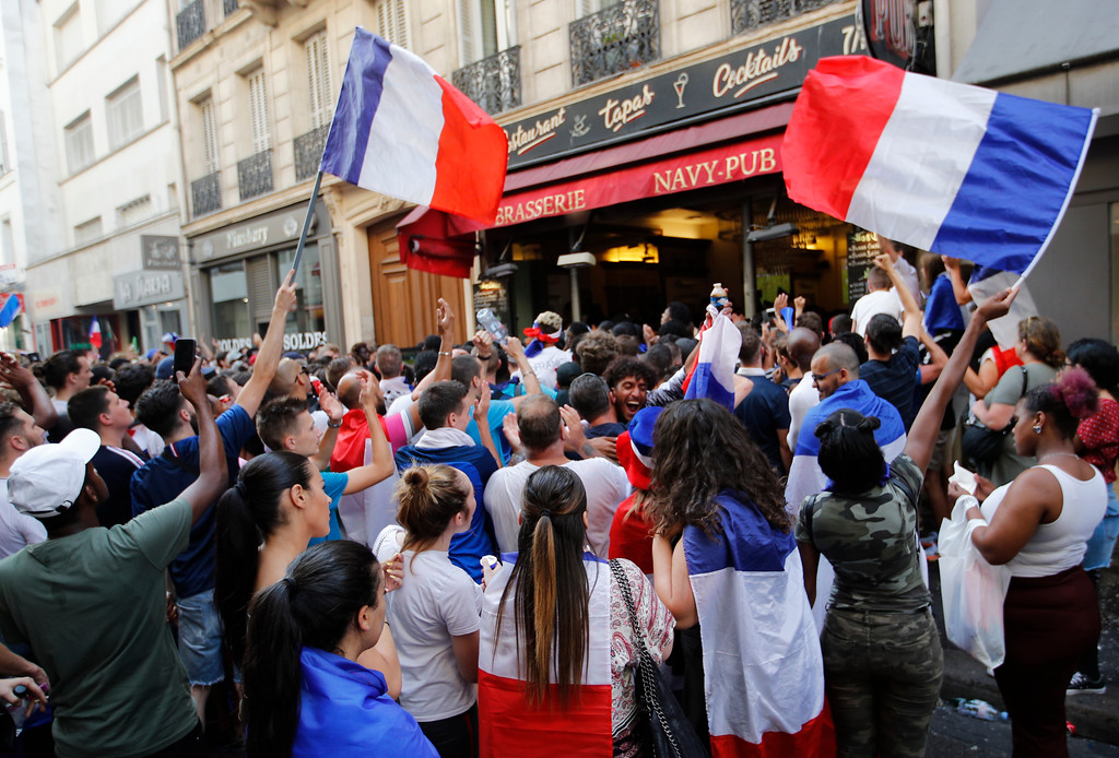 . French soccer team supporters wave French flags as they watch the soccer World Cup final match between France and Croatia, Sunday, July 15, 2018 in a cafe in Paris. (AP Photo/Francois Mori)