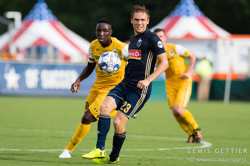 Nashville SC midfielder Bolu Akinyode (30) and North Carolina FC midfielder Zach Steinberger (23)
