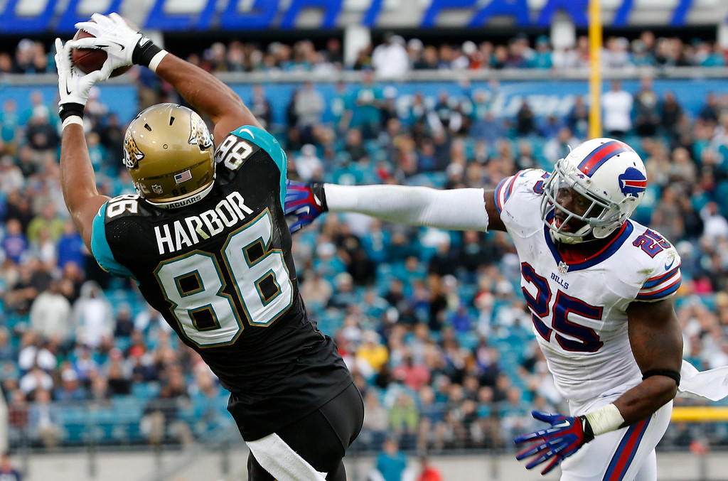 . Clay Harbor #86 of the Jacksonville Jaguars makes a reception against  Da\'Norris Searcy #25 of the Buffalo Bills during the game at EverBank Field on December 15, 2013 in Jacksonville, Florida.  (Photo by Sam Greenwood/Getty Images)