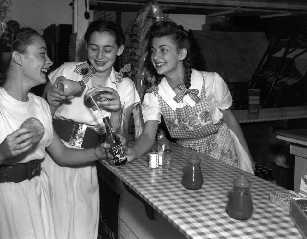 . Three teenage girls at a Minnesota State Fair food counter with a 7-Up bottle and burger buns in 1947. Photo from the Collection of the Minnesota Historical Society, courtesy of the Minnesota State Fair.