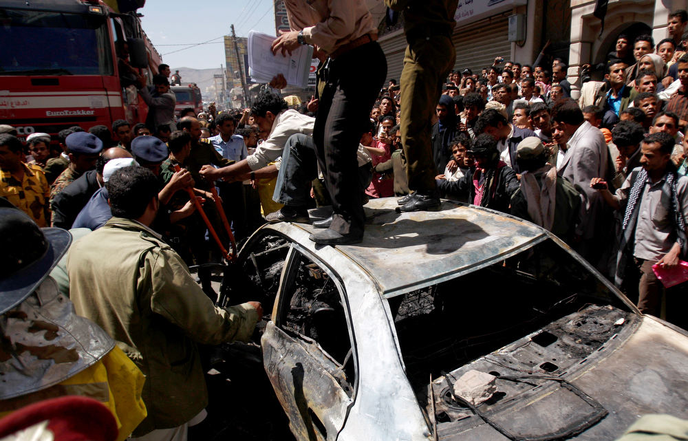 . Yemeni civilians and first responders try to recover charred bodies of the driver and passengers on the wreckage of a burnt taxi at the site of a plane crash in Sanaa, Yemen, Tuesday, Feb. 19, 2013. A Yemeni official says a military plane on a training exercise crashed into a neighborhood in the country\'s capital, Sanaa, killing and injuring scores of people. (AP Photo/Hani Mohammed)