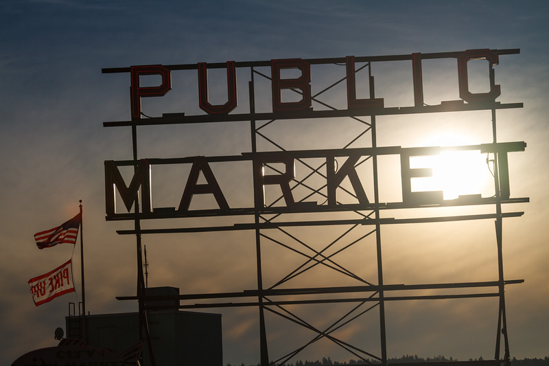 Public market sign an American flag backlit by the sun - Downtown Seattle, Seattle, Washington, United States (US)