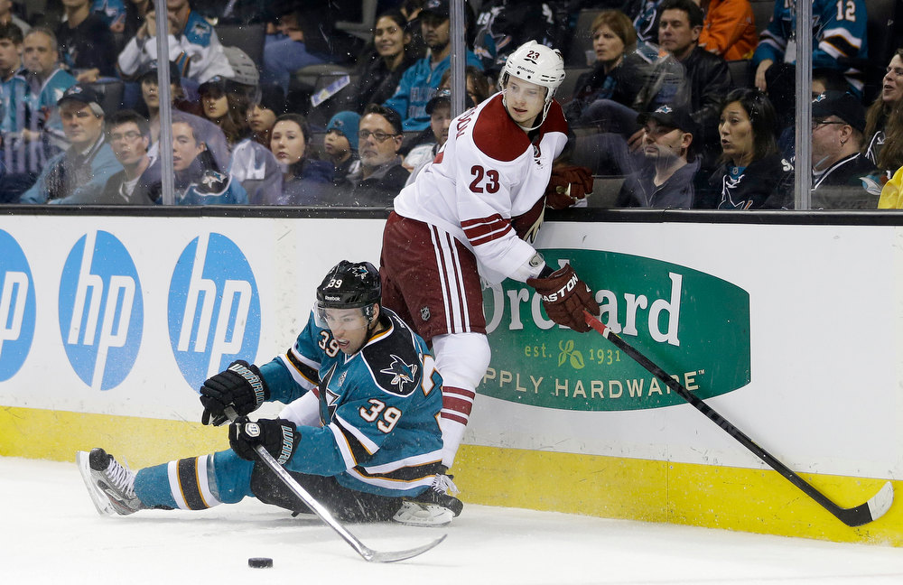 Description of . San Jose Sharks center Logan Couture (39) reaches for the puck next to Phoenix Coyotes defenseman Oliver Ekman-Larsson, of Sweden, during the first period of an NHL hockey game in San Jose, Calif., Thursday, Jan. 24, 2013. (AP Photo/Marcio Jose Sanchez)