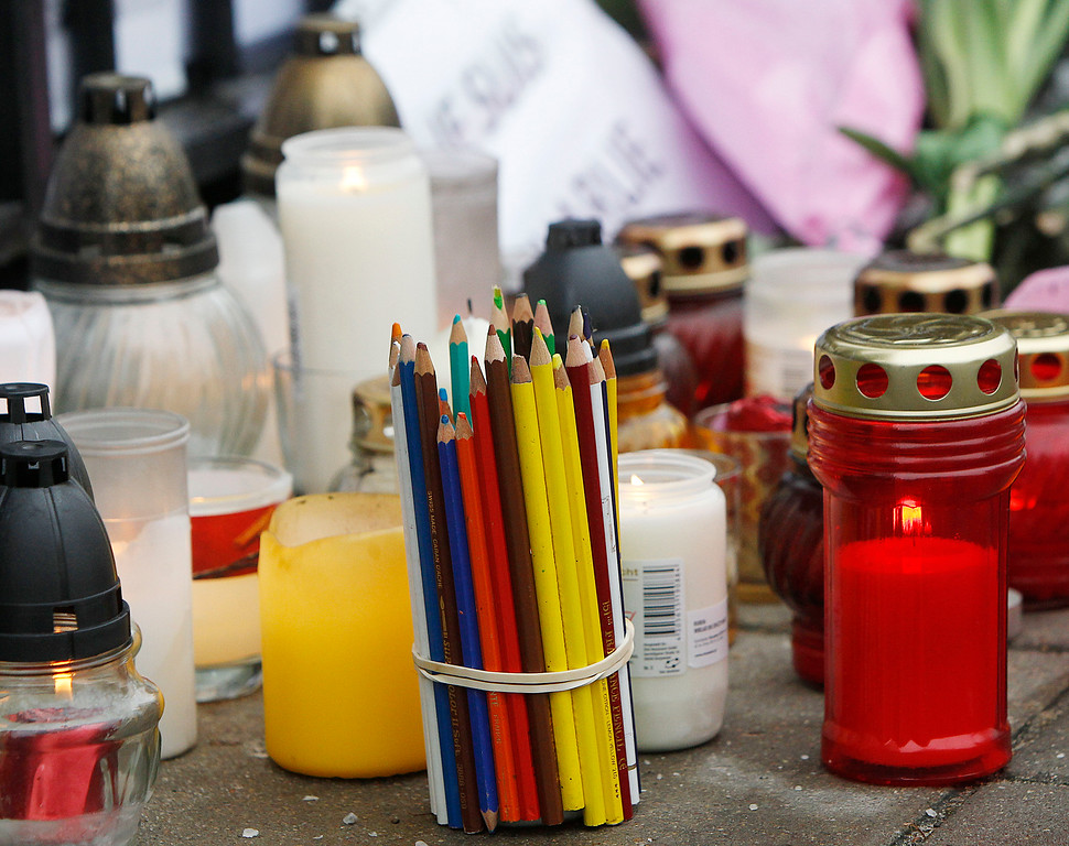 . Candles, colored crayons and flowers placed before the French embassy in Warsaw, Poland, Thursday, Jan. 8, 2015, for the 12 journalists, cartoonists and policemen methodically killed Wednesday by two heavily armed attackers at a satirical newspaper in Paris that caricatured the Prophet Muhammad. (AP Photo/Czarek Sokolowski)