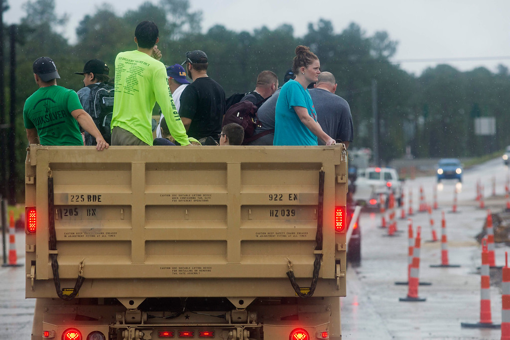 . Members of the Louisiana Army National Guard rescue people from rising floodwater near Walker, La., after heavy rains inundated the region, Sunday, Aug. 14, 2016. (AP Photo/Max Becherer)