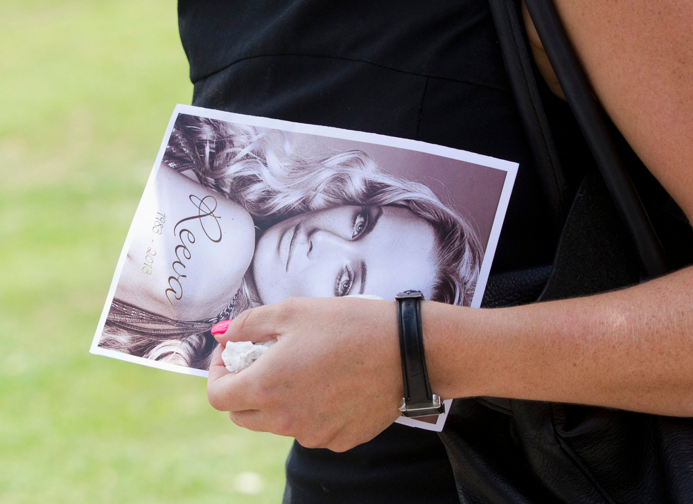 . A mourner leaves, holding a picture of model Reeva Steenkamp, after her memorial service at the Victoria Park Crematorium in Port Elizabeth February 19, 2013. Steenkamp\'s boyfriend Olympic and Paralympic athlete Oscar Pistorius has been charged with her murder. REUTERS/Rogan Ward