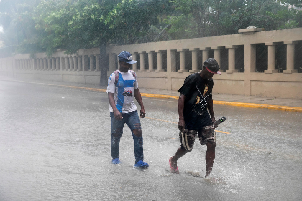 . Men wade through a flooded Alemania Avenue as Hurricane Maria reaches the coast of Bavaro, Dominican Republic, Wednesday, Sept. 20, 2017. (AP Photo/Tatiana Fernandez)