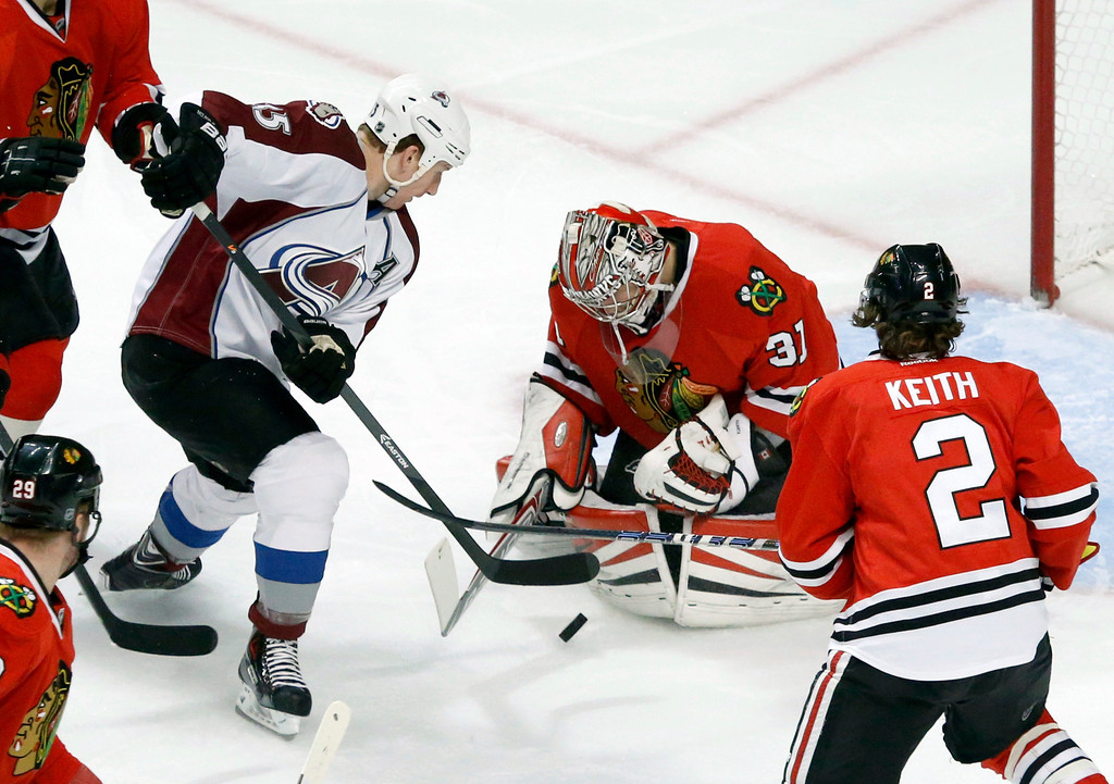 . Chicago Blackhawks goalie Antti Raanta (31) makes a save on a shot by Colorado Avalanche left wing Cody McLeod, as defenseman Duncan Keith (2) watches during the first period of an NHL hockey game Friday, Dec. 27, 2013, in Chicago. (AP Photo/Charles Rex Arbogast)