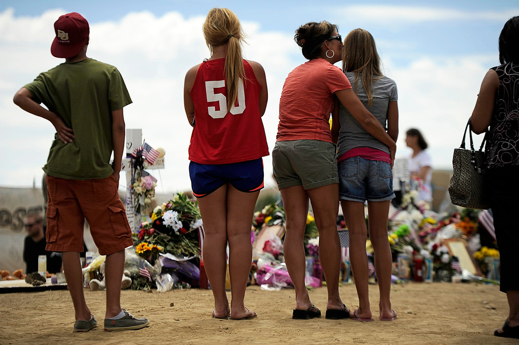 . Michael, 14, and Allie, 15, look at the memorial as their mother Susan Brust kisses Tessa 11, while they visit the memorial for the victims of the Century 16 Theater shooting at the corner of Sable Boulevard and Centerpoint Drive in Aurora, Colorado Wednesday, July 25,  2012. �We want to feel closer to them and to say our prayers, and see the outpouring of love from the community. It\'s amazing,� said Susan Brust of Castle Pines. Joe Amon, The Denver Post