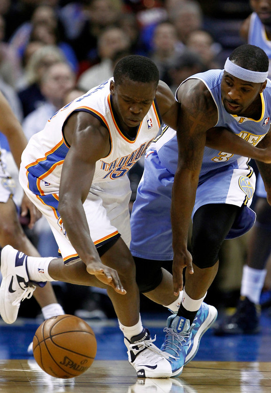 . Oklahoma City Thunder guard Reggie Jackson, left, and Denver Nuggets guard Ty Lawson, right, go for a loose ball during the second quarter of an NBA basketball game in Oklahoma City, Wednesday, Jan. 16, 2013.  (AP Photo/Alonzo Adams)