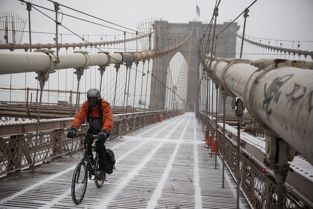 . A man rides his bike across the Brooklyn Bridge during a snow storm that is moving through the Northeast on January 21, 2014 in New York City.  (Photo by Andrew Burton/Getty Images)