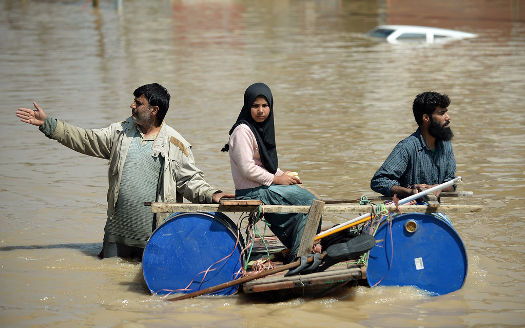 ". Kashmiri men transport a stranded girl on a makeshift raft through the floodwaters in Srinagar on September 10, 2014.  Anger mounted over the slow pace of rescue operations in Indian Kashmir as officials said they were ""overwhelmed\"" by the scale of deadly flooding that has left hundreds of thousands stranded in the Himalayan region and neighboring Pakistan.  AFP PHOTO/ PUNIT PARANJPE/AFP/Getty Images"