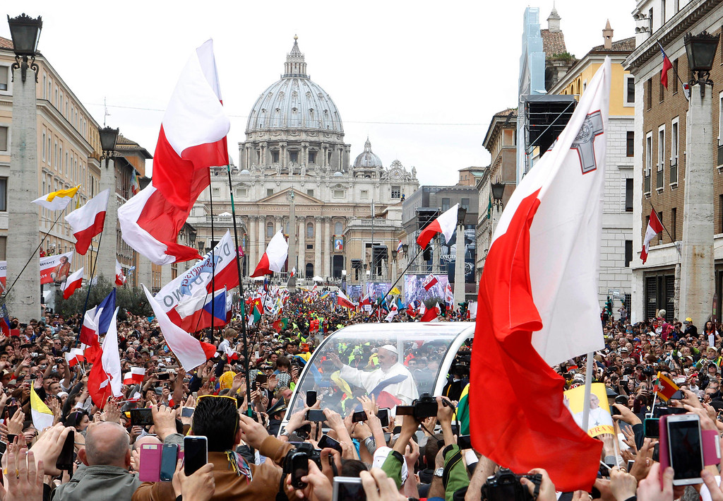 . Pope Francis greets faithful as he is driven through the crowd along Via della Conciliazione after celebrating the ceremony for the canonizations of Pope John XXIII and Pope John Paul II in St. Peter\'s Square, at the Vatican, Sunday, April 27, 2014. Pope Francis declared his two predecessors John XXIII and John Paul II saints before some 800,000 people on Sunday, an unprecedented ceremony made even more historic by the presence in St. Peter\'s Square of emeritus Pope Benedict XVI. (AP Photo/Riccardo De Luca)