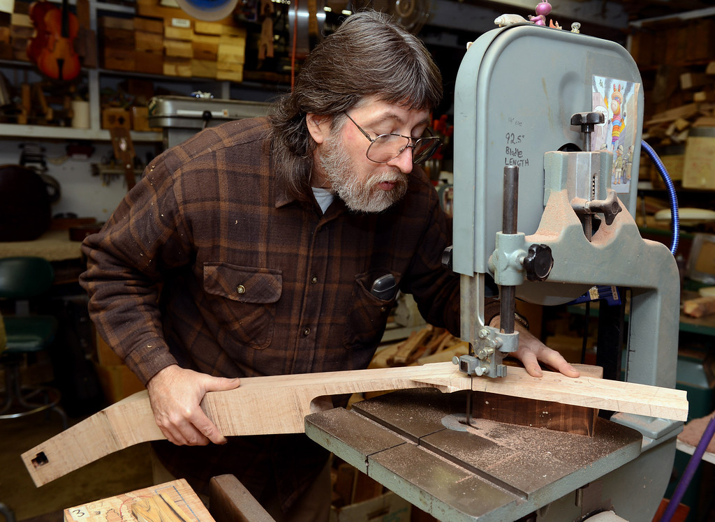 . John Jordan uses a band saw to cut the neck of an electric upright bass he is handcrafting from maple in his Concord, Calif.  workshop on Monday, Jan. 28, 2013.  The owner requested a thinner neck on the instrument and Jordan customizes it.  (Susan Tripp Pollard/Staff)