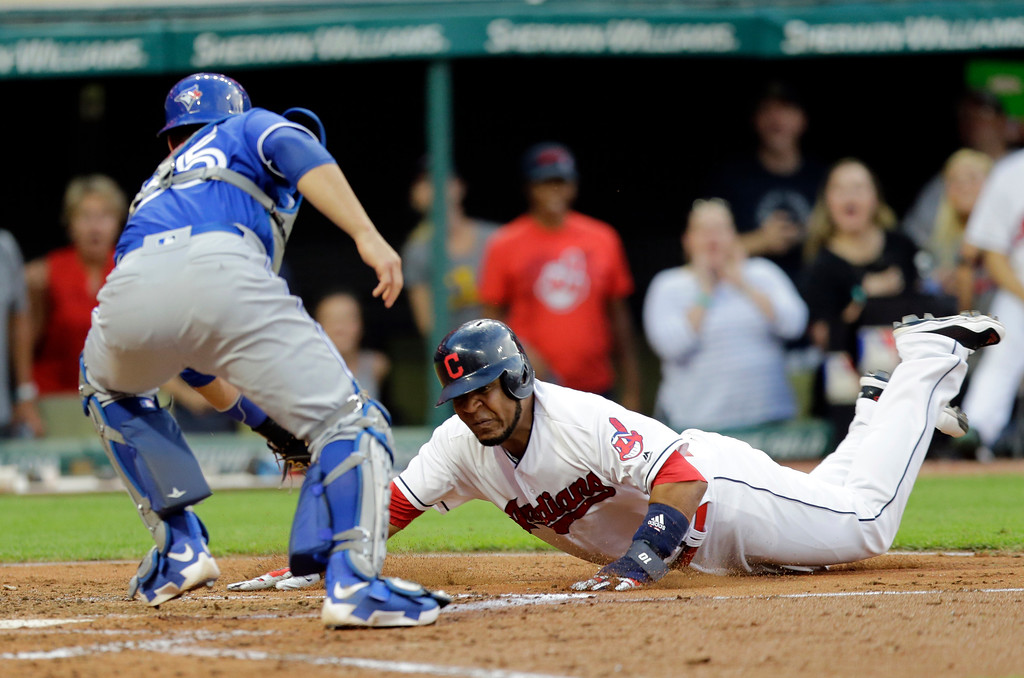 . Cleveland Indians\' Edwin Encarnacion is tagged out at home plate by Toronto Blue Jays catcher Russell Martin in the fourth inning of a baseball game, Friday, July 21, 2017, in Cleveland. (AP Photo/Tony Dejak)